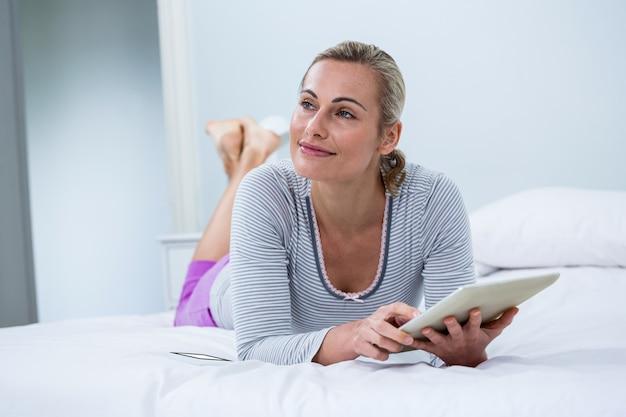 Улыбается женщина с цифровой планшет, лежа на кровати