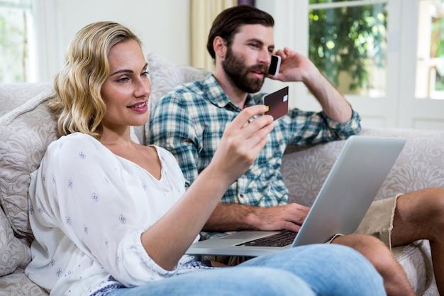 ノートパソコンと電話で話している人によってデビットカードを保持している女性