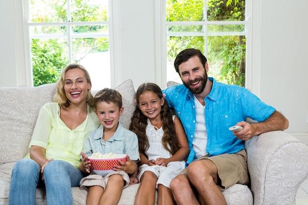 Портрет счастливой семьи смеется во время просмотра телевизора