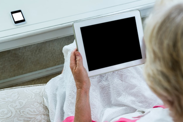 Взгляд высокого угла старшей женщины держа цифровую таблетку