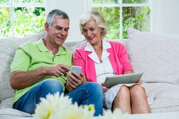 Муж показывает мобильный телефон старшей женщине на диване