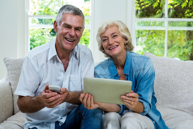 タブレットとリビングルームでの携帯電話と年配のカップルの肖像画