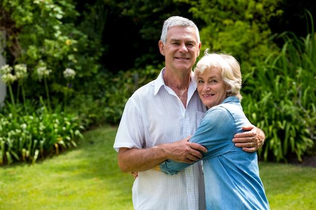 Портрет старших пар, охватывающей на заднем дворе