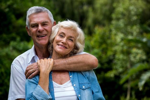 Старший мужчина обнимает жену сзади в заднем дворе