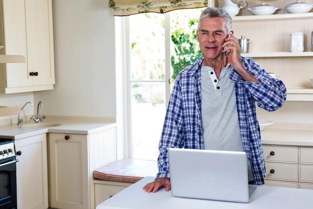 年配の男性が台所に立っている間を呼び出す