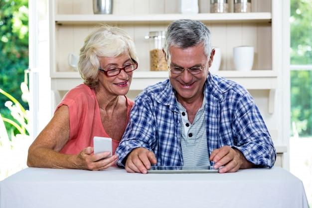 キッチンで携帯電話とデジタルタブレットを使用して年配のカップル