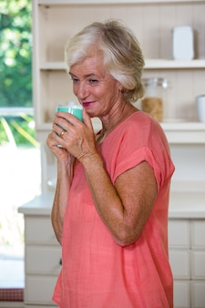 台所でコーヒーを飲んで思慮深い年配の女性