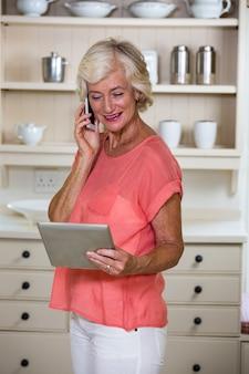 Старшая женщина используя цифровую таблетку и мобильный телефон в кухне
