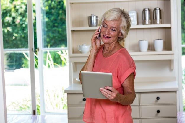 Старшая женщина используя цифровую таблетку и мобильный телефон
