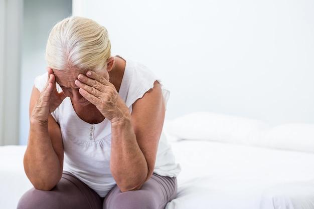 寝室に座って手で頭を持つ年配の女性