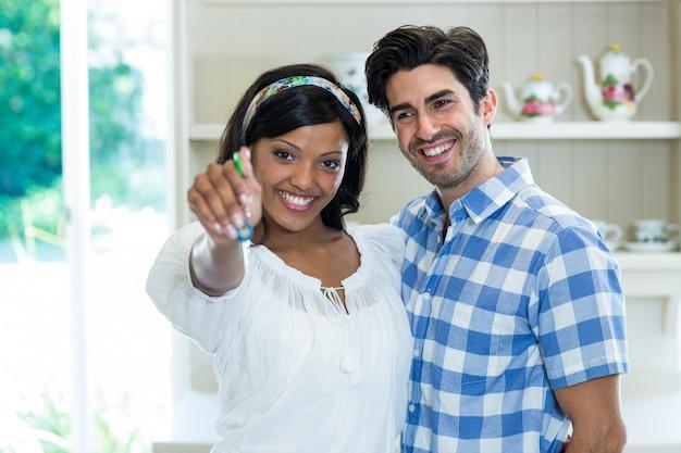 Счастливая молодая пара показывает ключ от своего нового дома