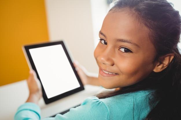 Девушка улыбается и с помощью планшета