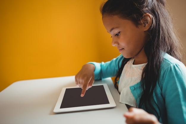 Маленькая девочка с помощью планшета