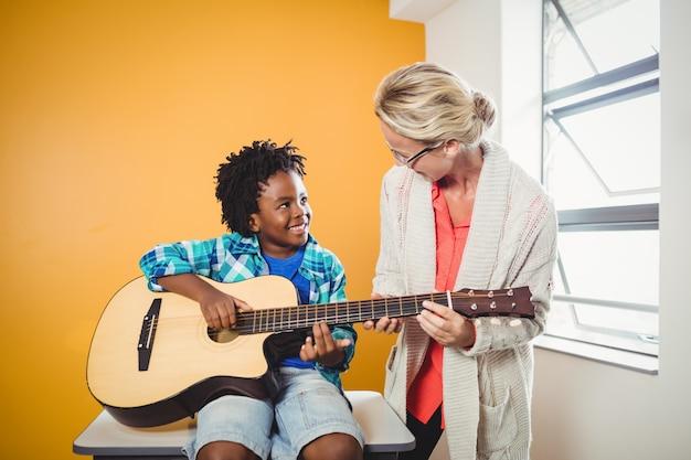 ギターの弾き方を学ぶ少年