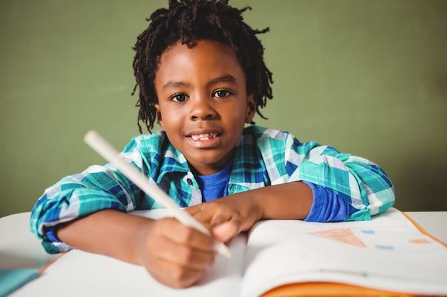 彼のノートに書いている少年