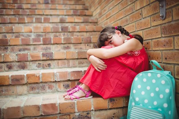 レンガの壁に座っている悲しいブルネットの少女