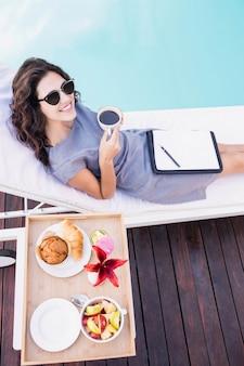 Портрет молодой женщины с чашкой чая и отдыха на шезлонге возле бассейна