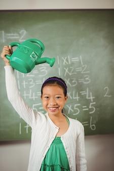 彼女の水まき缶を使用して笑顔の学校の女の子