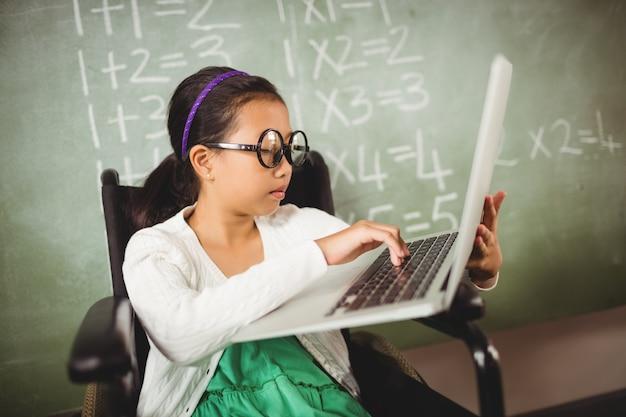 彼女のラップトップに入力する大きな眼鏡の少女