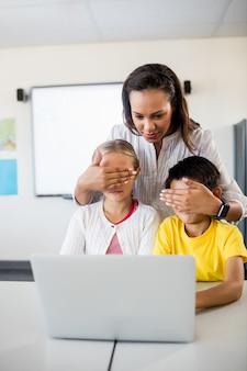 コンピューターの前で生徒の目を覆っている先生