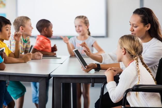 Учитель на уроке с планшетным пк