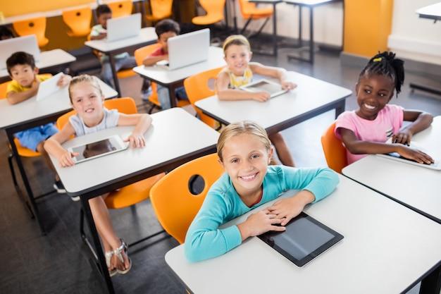 Аэрофотоснимок учеников, работающих с ноутбуком и планшетным пк