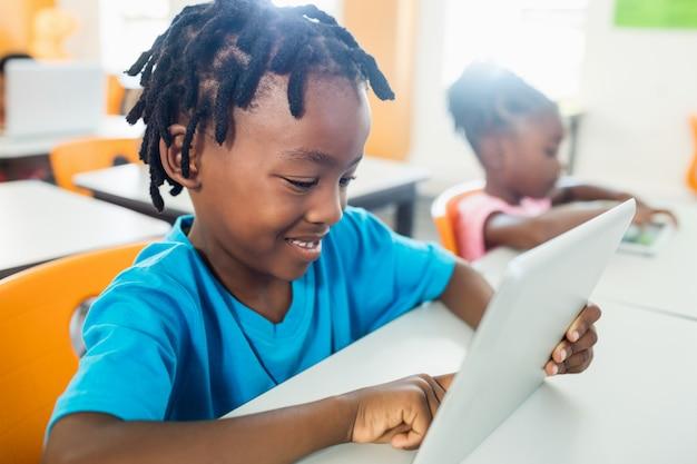 Вид сбоку ученика с помощью планшетного пк в классе