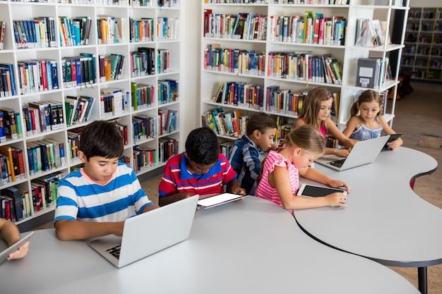 Вид сбоку ученика с помощью ноутбука и планшетного пк