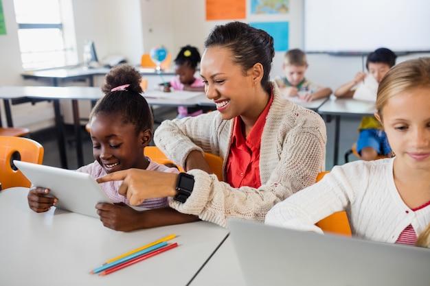 Учитель помогает с планшетным компьютером