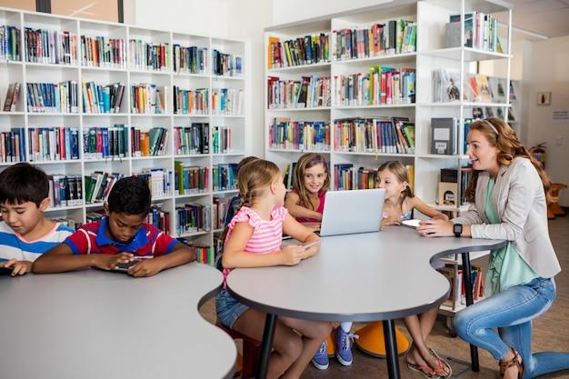 Учитель с помощью компьютера с учениками