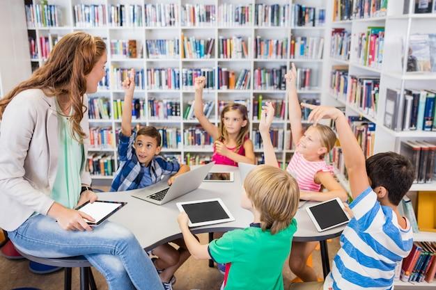 Молодая милая учительница имея урок к детям с их таблеткой