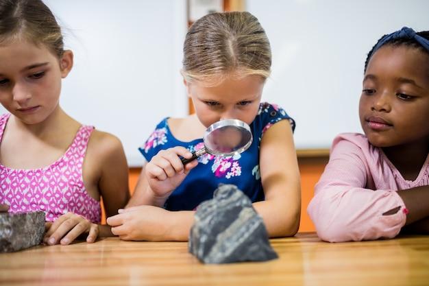 虫眼鏡で化石を見ている子供