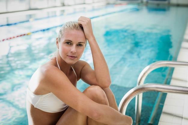 プールの端に座っている魅力的な女性