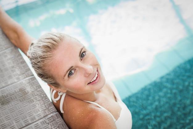魅力的な女性はプールの端で休む