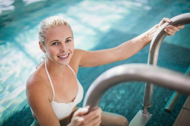 魅力的な女性はプールで水から抜け出す