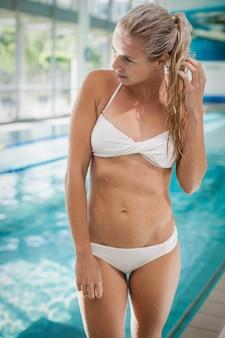 魅力的な女性は立っているとプールを見ています