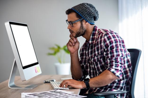 Серьезный случайный человек, работающий на компьютерный стол