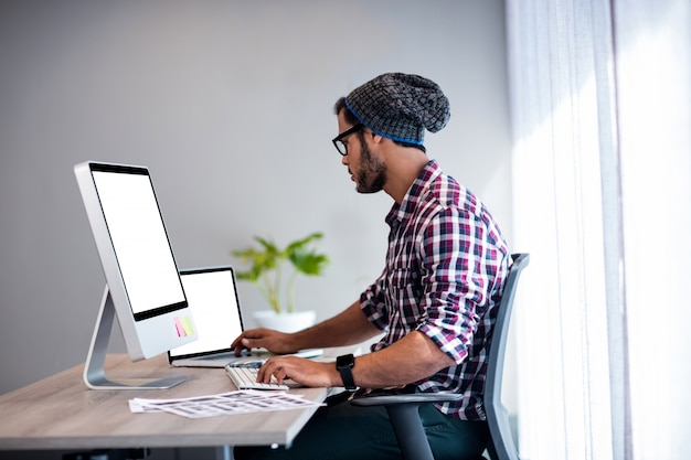 Серьезный хипстер, работающий за компьютерным столом