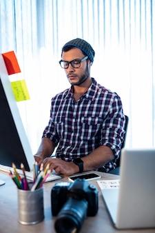 コンピューターの机で働く写真家