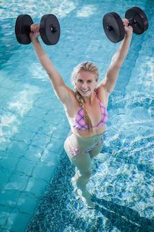 Гантели привлекательной женщины поднимаясь в бассейне