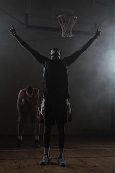 勝利のバスケットボール選手が腕を上げる