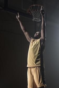 勝利のために腕を投げるバスケットボール選手の肖像画