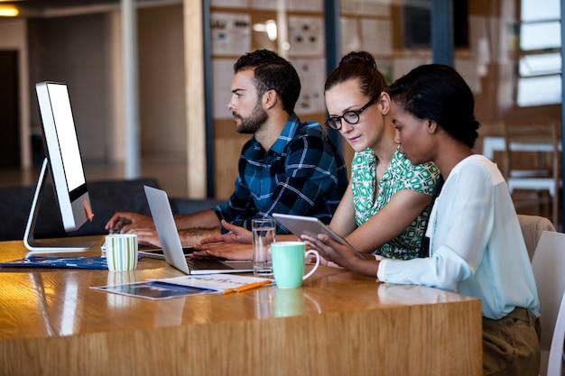 コンピューターの机に座ってビジネス人々