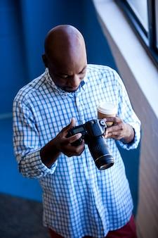 彼のカメラを探している写真家のクローズアップ表示