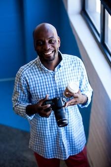 カメラでポーズをとって笑顔の写真家