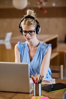 コンピューターでの作業中に音楽を聴く女性の肖像