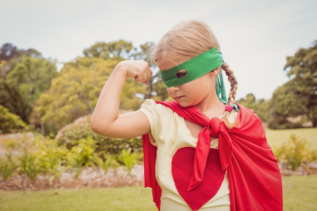 Маленькая девочка в костюме супергероя сжимая бицепс