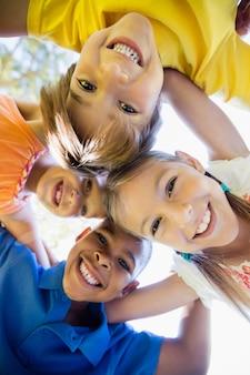 サークルでハドルを形成する子どもたちの笑顔