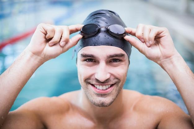 水泳帽とゴーグルを着ているハンサムな男