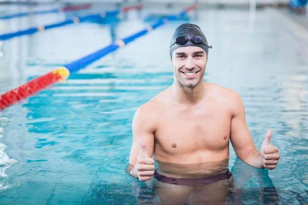 プールで水に親指を持つハンサムな男